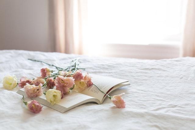 rozevřená kniha a květiny na posteli