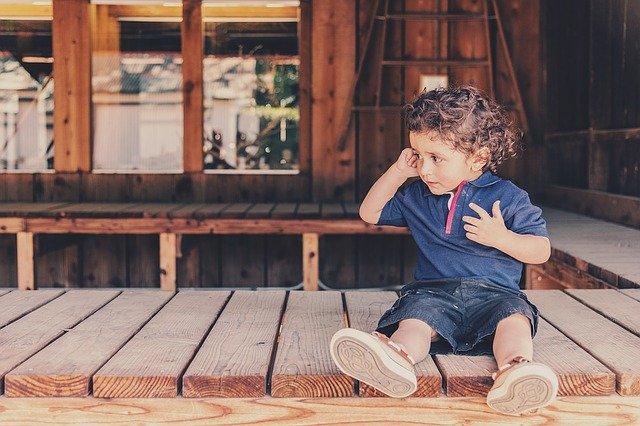 malý chlapec sedící na zemi ve stodole
