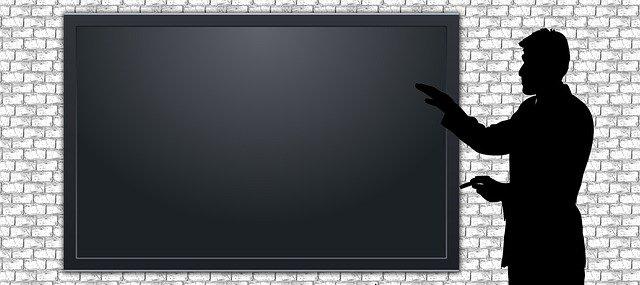 Silueta muže ukazujícího směrem k tabuli na stěně